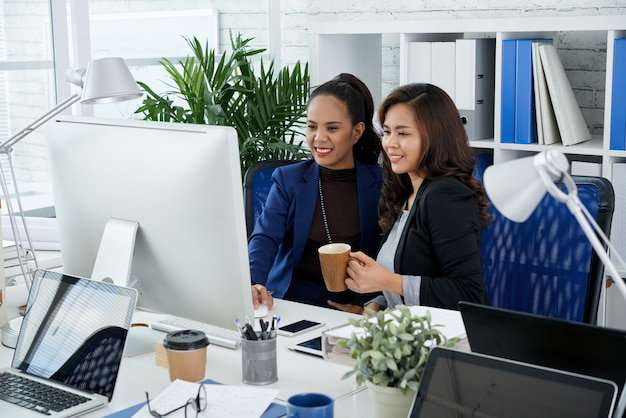 Happy proud young businesswoman showing her presentation to colleague with cup of coffee