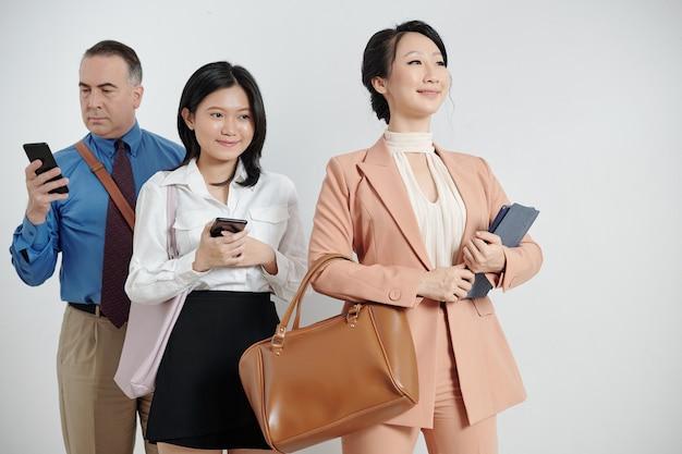 태블릿 컴퓨터와 함께 서 있는 자랑스러운 젊은 여성 사업가, 뒤에 스마트폰을 들고 있는 동료
