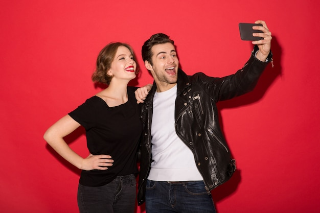 Happy punk couple posing and making selfie on smartphone