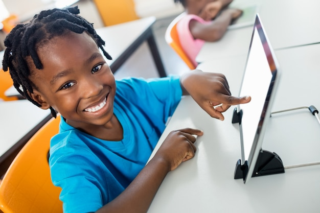 Happy pupil using tablet pc in classroom