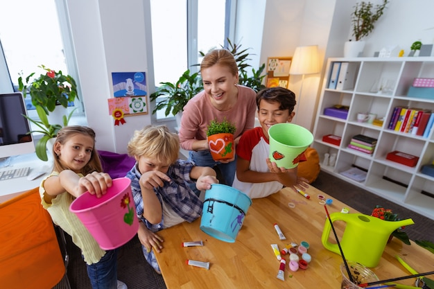 幸せな生徒。生徒たちは、色を塗った後、植物用のクールなバケツを見せて幸せを感じています
