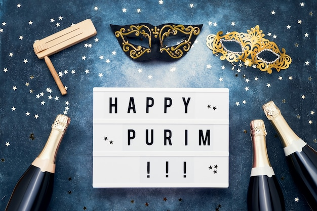Happy purim written in light box, champagne bottles, carnival mask and wooden gragger on blue