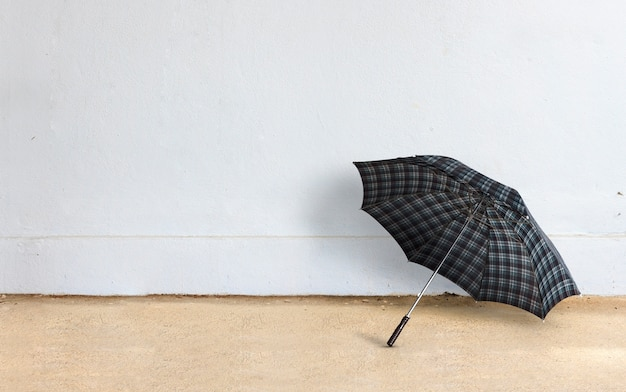 Happy rainy day concept. umbrella with brick wall background