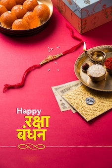 Happy raksha bandhan or rakhi greeting card using designer thread, diya, pooja thali, gift box, indian paper currency notes and sweets etc. moody lighting, selective focus