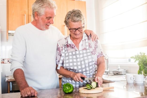 愛の大人の高齢者の幸せな本物のカップルは、健康のために健康的な食べ物を食べるために野菜を切る台所で家の活動を楽しんでいる男性と女性を引退しました