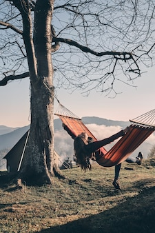 Happy!  rear view of young woman keeping arms outstretched while relaxing in hammock outdoors