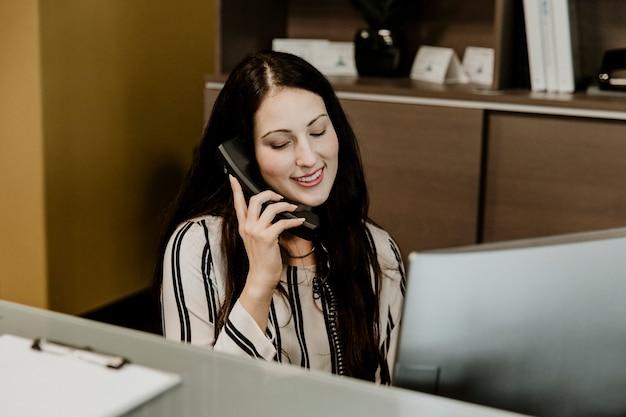 Happy receptionist  on the telephone