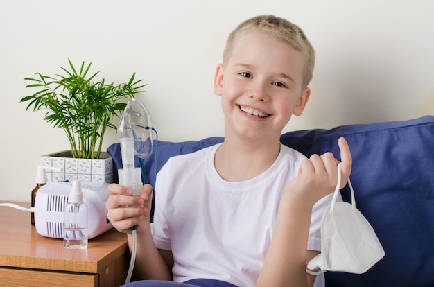 Happy recovered boy holds a medical protective mask and a nebulizer mask