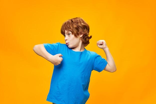 Счастливый рыжий мальчик в синей футболке на желтом танцует и смотрит в сторону