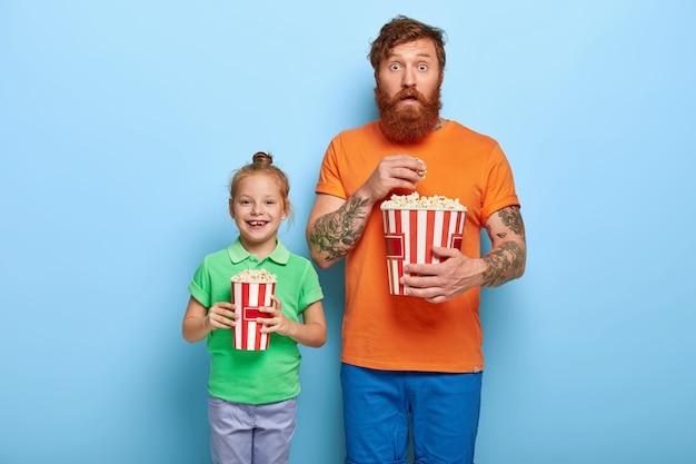 幸せな赤い髪の子供と彼女のお父さんはおいしいポップコーンのバケツを持っています