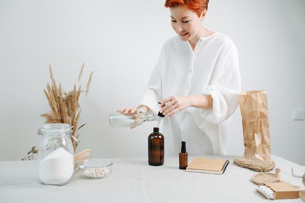 Счастливый рыжий женский химик готовит смесь для экологически чистой косметики на столе. добавление жидкости в обычную коричневую пластиковую бутылку с помощью пипетки