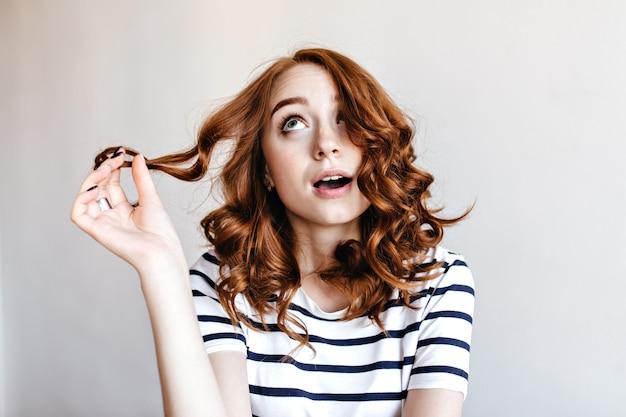 행복 한 red-haired 소녀 그녀의 곱슬 머리와 함께 연주 하 고 올려. 꿈꾸는 생강 아가씨는 줄무늬 티셔츠를 입는다.