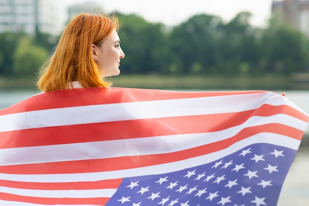 Happy red haired girl with usa national flag on her shoulders. positive young woman celebrating united states independence day.
