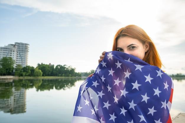 彼女の肩にアメリカの国旗を持つ幸せな赤い髪の少女。アメリカ合衆国の独立記念日を祝うポジティブな若い女性。