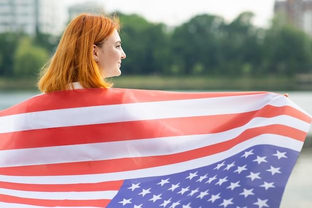 Счастливая рыжеволосая девушка с национальным флагом сша на ее плечах. положительная молодая женщина празднуя день независимости соединенных штатов.