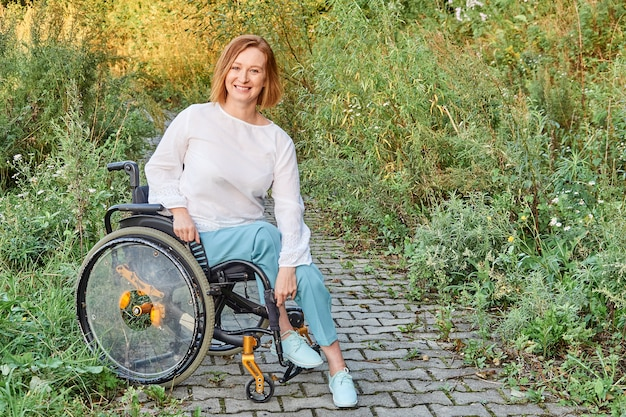 Happy red-haired inclusive woman in a wheelchair enjoying sunny weather in the fall.