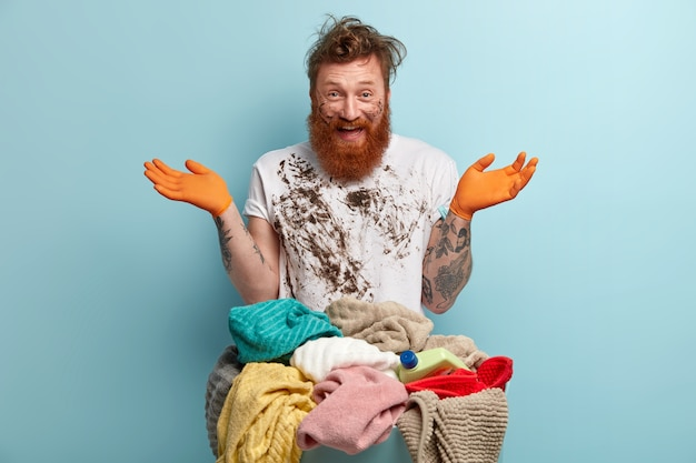 Happy red haired man with thick bristle, spreads hands, has fun after doing laundry at home