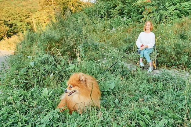 秋の晴れた天気を楽しんで、彼女の犬と一緒に散歩のために車椅子で幸せな赤毛の女性。
