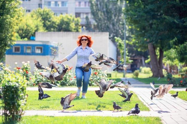 Счастливая рыжеволосая женщина бежит по парку и гонится за голубями