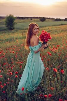 꽃 양 귀 비 필드에 손에 꽃다발과 함께 산책하는 행복 한 빨간 머리 여자