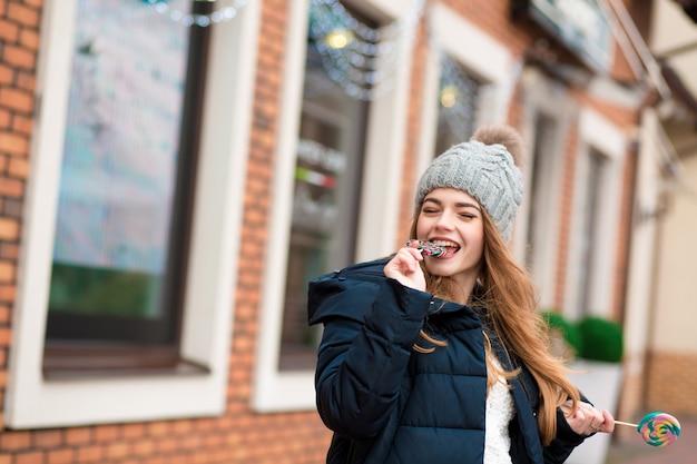 灰色のニット帽をかぶって、クリスマスのキャンディーを食べる幸せな赤い髪の若い女性