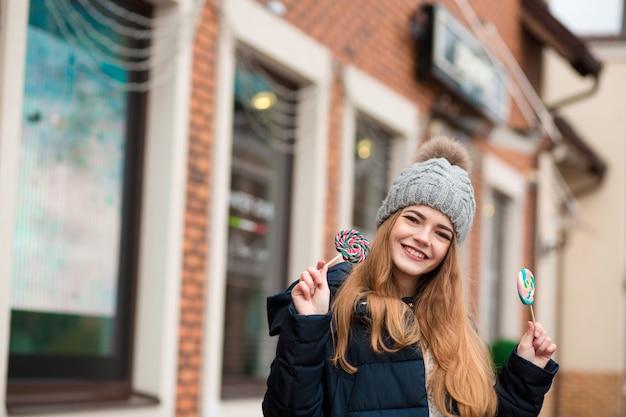 灰色のニット帽をかぶって、店の窓の近くでカラフルなクリスマスのキャンディーを保持している幸せな赤い髪の若い女性