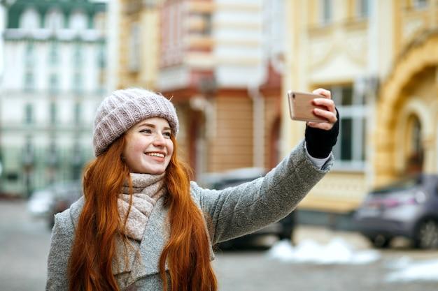 彼女の携帯電話で自分撮りをしている冬のアパレルの幸せな赤い頭のモデル。テキスト用のスペース