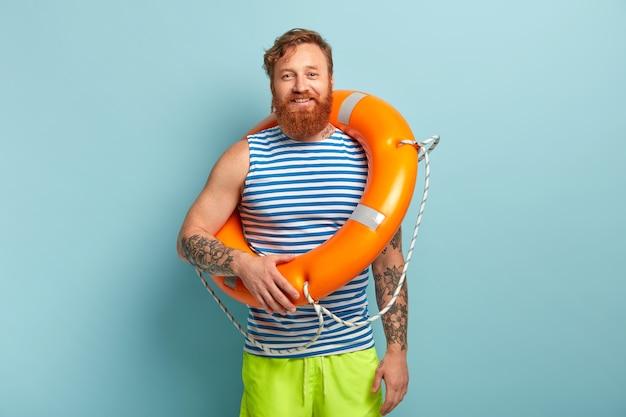 행복한 redhaired 남성 휴가객은 선원 조끼를 입고 짧고 바다에서 수영을 구하기 위해 주황색 구명 부표를 운반합니다.