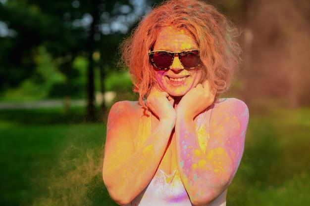 공원에서 다채로운 건조 holi 페인트로 덮여 포즈 흰색 t 셔츠를 입고 행복 redhaired 여자