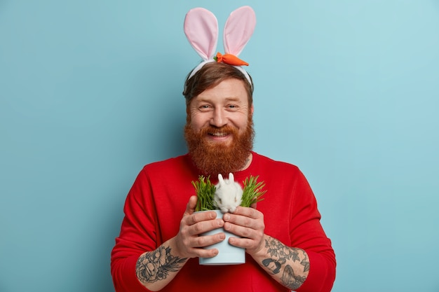 행복 한 빨간 머리 수염 된 백인 남자 토끼 귀에 신선한 녹색 잔디와 작은 냄비에 흰색 부활절 토끼를 보유 하 고 기꺼이, 파란색 벽에 고립 된 보인다. 봄 휴가 개념