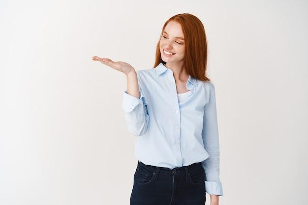 특별 프로모션을 들고 있는 행복한 빨간 머리 여성, 만족스러운 미소로 제품을 바라보며 흰 벽 위에 서 있습니다