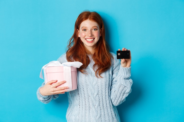 Happy redhead girl buying gifts with credit card, holding box with present and smiling, standing over blue background.