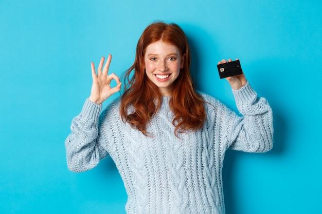 스웨터를 입은 행복한 빨간 머리 소녀는 신용 카드와 ok 사인을 보여주고, 은행 제안을 추천하고, 파란색 배경 위에 서 있습니다.