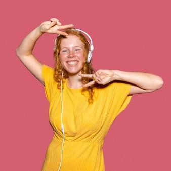 Счастливая рыжая девушка слушает музыку через наушники
