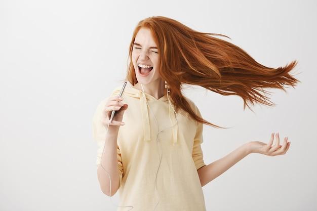 Счастливая рыжая девушка играет в караоке-приложение на смартфоне и поет песню в наушниках