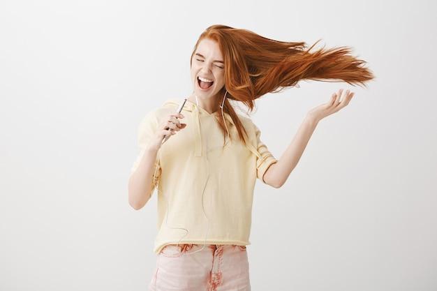 Happy redhead girl playing karaoke app game on smartphone, singing song in earphones