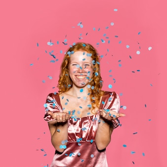 Happy redhead girl throwing confetti