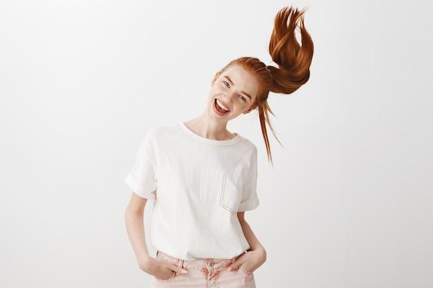 Счастливая рыжая девушка плетет хвостик и беззаботно улыбается
