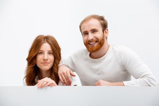 Happy redhead girlfriend and boyfriend smiling, hide
