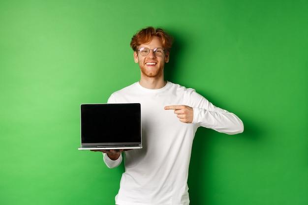 행복 한 빨간 머리 남자 안경에 흰색 긴 소매 티셔츠, 빈 노트북 화면에서 손가락을 가리키고 웃 고, 녹색 배경 위에 서 서.