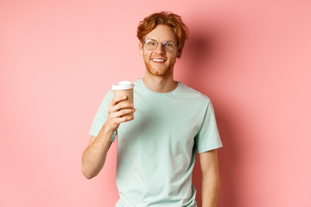 Happy redhead man in glasses and t-shirt drinking coffee and smiling, enjoying lunch break, holding takeaway cup, standing over pink background.