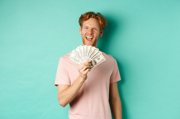 티셔츠를 입은 행복한 빨간 머리 남자는 돈을 달러로 표시하고 웃고, 현금을 획득한 후 우스꽝스러운 얼굴을 하고, 청록색 배경 위에 서 있습니다.