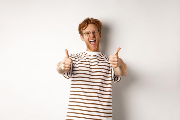 Счастливый рыжий человек кричит да и показывает палец вверх, одобряет и хвалит потрясающую компанию, стоя на белом фоне.