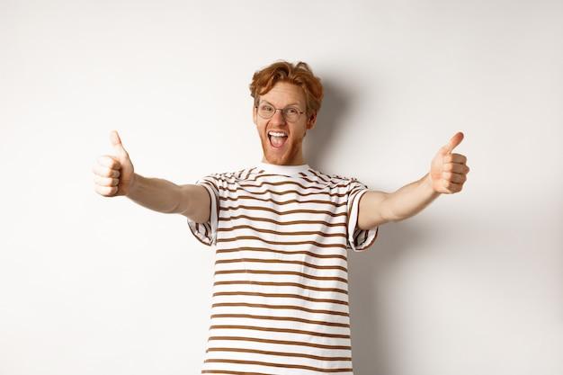 Счастливый рыжий человек кричит да и показывает палец вверх, одобряет и хвалит отличную компанию, стоя на белом фоне.