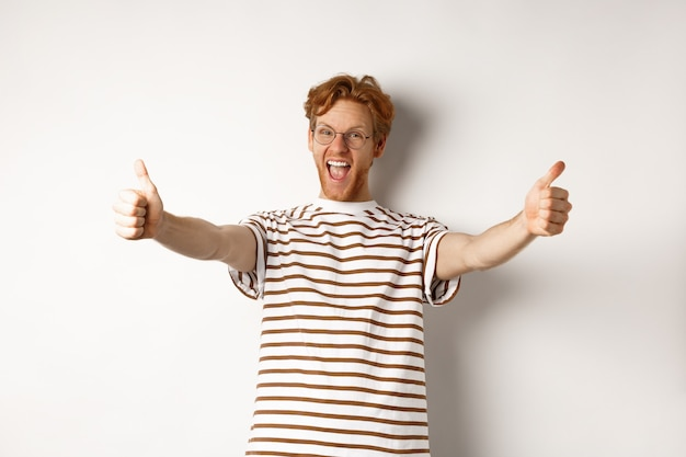 Happy redhead man scream yes and showing thumbs-up, approve and praise excellent company, standing over white background.