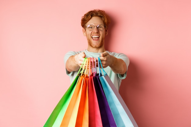 Happy redhead man stretch out hands with shopping bags, give you gifts, standing over pink background.