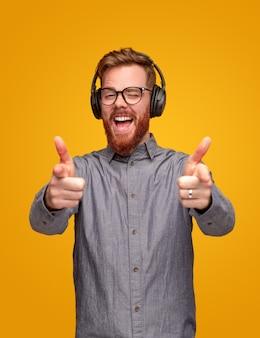 ヘッドフォンで良い音楽を聴き、黄色の背景に対してカメラを指しているひげを持つ幸せな赤毛の男
