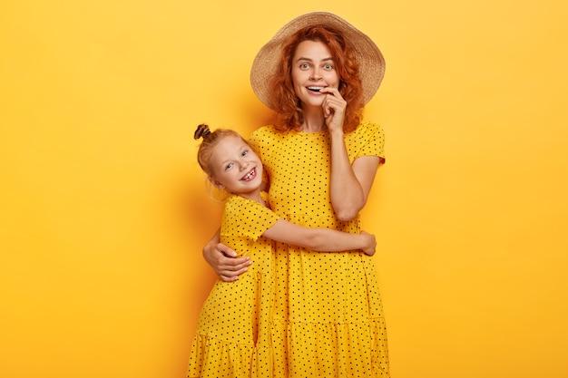 비슷한 드레스를 입고 포즈를 취하는 행복 한 빨간 머리 엄마와 딸