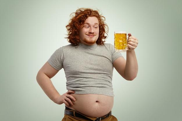Счастливый рыжий грузный мужчина с большим животом, торчащим из его укороченной футболки, держит стакан холодного пива, смотрит в ожидании, нетерпеливый, чтобы почувствовать его хороший вкус, отдыхая дома после работы