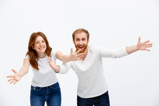 Счастливые рыжие родители протягивают руки для объятий, улыбаясь